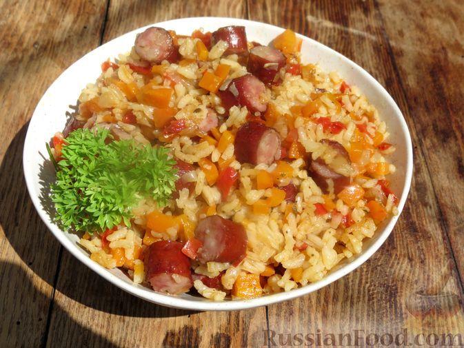 Фото к рецепту: Рис с сосисками и овощами, на сковороде